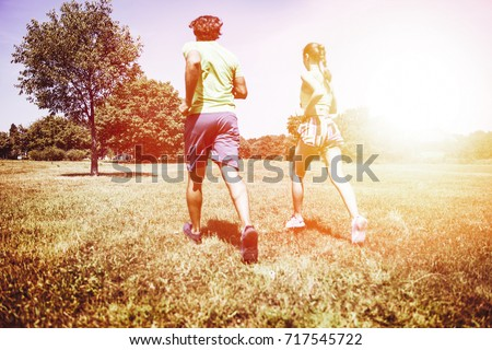 View at young couple running in the park on a sunny day #717545722