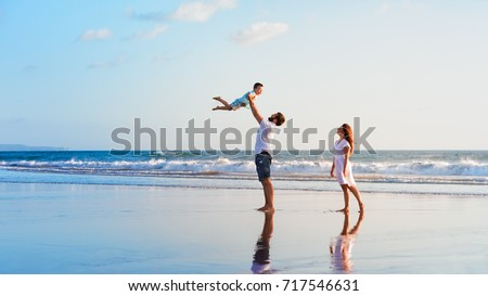 Happy family holidays. Joyful father, mother, baby son walk with fun along edge of sunset sea surf on black sand beach. Active parents and people outdoor activity on summer vacations with children.