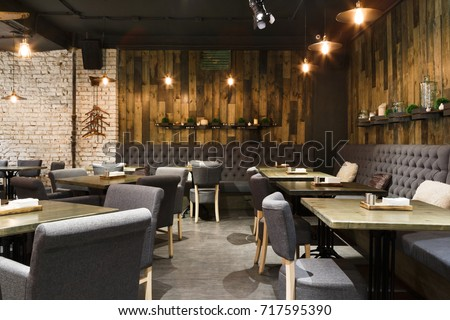 Cozy wooden interior of restaurant, copy space. Comfortable modern dining place, contemporary design background Royalty-Free Stock Photo #717595390