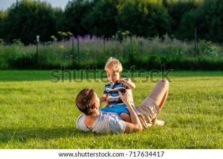 Happy man and child having fun outdoor on meadow.  Family lifestyle scene of father and son resting together on green grass in the park.  #717634417