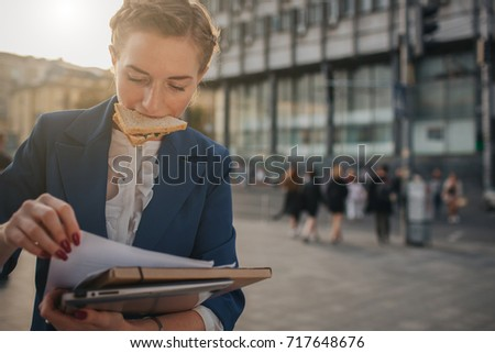 Busy woman is in a hurry, she does not have time, she is going to eat snack on the go. Worker eating and talking on the phone at the same time..  Business female person. Royalty-Free Stock Photo #717648676