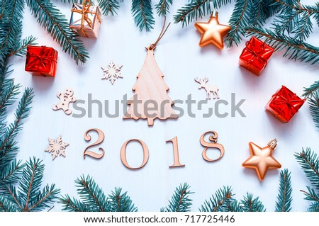 New Year 2018 background with figures, Christmas toys, with frame of blue fir branches. New Year 2018 composition. Flat lay, top view of New Year 2018 festive still life #717725446