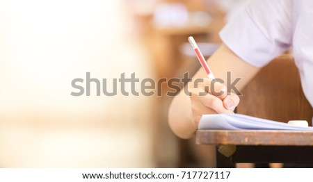 soft focus.high school or university student holding pencil writing on paper answer sheet.sitting on lecture chair taking final exam attending in examination room or classroom.student in uniform. #717727117