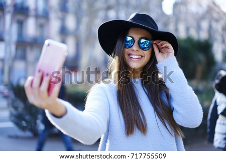 Charming cheerful female tourist in trendy sunglasses taking self portrait with cellular camera during standing at spring urban setting.Young cute positive woman having recreation using technology