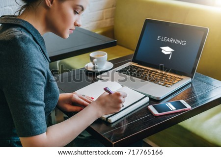 Young businesswoman sitting at table in cafe in front of laptop with inscription on screen e-learning and image of square academic cap and making notes in notebook,diary. Online education,e-learning. #717765166