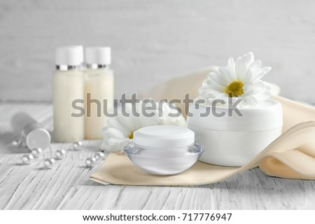 Composition with skin care products and chamomile flowers on wooden table #717776947