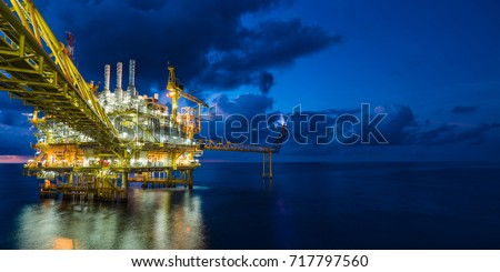 Panorama of oil and gas central processing platform in sun set where produced, treat the hydrocarbon then sent to refinery , petrochemical , power generation plant and tanker barge for export. Royalty-Free Stock Photo #717797560
