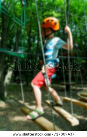 Active children's recreation. Climbing the rope park blurred abstract background #717809437