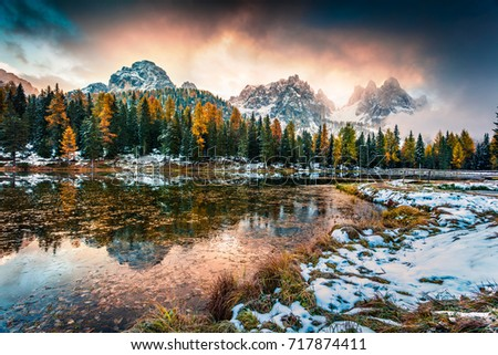 Dramatic sunrise on Antorno lake. Colorful autumn morning in Dolomite Alps, Province of Belluno, Italy, Europe. Artistic style post processed photo.