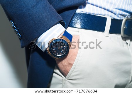 Closeup fashion image of luxury watch on wrist of man.body detail of a business man.Man's hand in a white shirt,blue jacket  in a pants pocket closeup. Tonal correction.Man posing in blue suit. Royalty-Free Stock Photo #717876634
