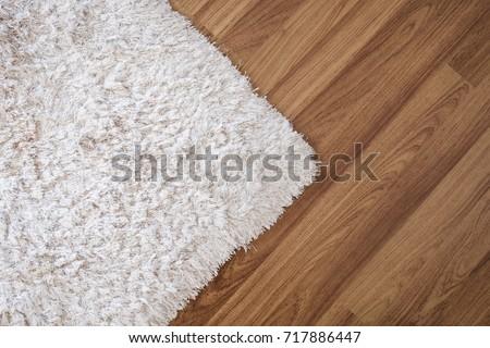 Close-up white carpet on laminate wood floor in living room, interior decoration #717886447