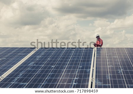engineer working on checking and maintenance electrical equipment ; engineer inspector working on examining electrical system of solar power plant  #717898459