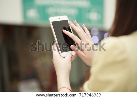 Beautiful female hands holding a mobile phone, indoor #717946939