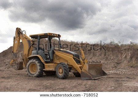Backhoe on a pile of dirt #718052