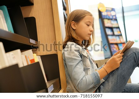 Young girl in book store reading comics Royalty-Free Stock Photo #718155097