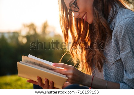Cropped image of smiling brunette woman in eyeglasses reading book in park #718159153