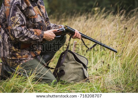 Hunter with a backpack and a hunting gun in the autumn forest. Man is charging a hunting rifle. Close up. #718208707