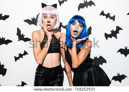 Picture of two emotional young women in halloween costumes on party over white background. Looking camera.