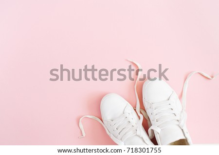 Fashion blog or magazine concept. White female sneakers on pink background. Flat lay, top view minimal background. #718301755