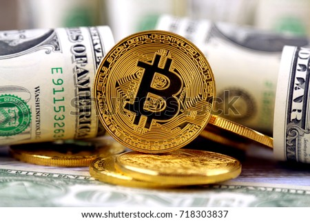 Physical version of Bitcoin (new virtual money) and banknotes of one dollar. Exchange bitcoin for a dollar. Conceptual image for worldwide cryptocurrency and digital payment system. #718303837
