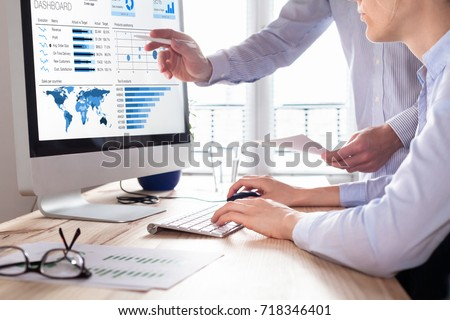 Team of financial people discussing a business analytics (BA) or intelligence (BI) dashboard on the computer screen showing sales and operations data statistics and key performance indicators (KPI) Royalty-Free Stock Photo #718346401