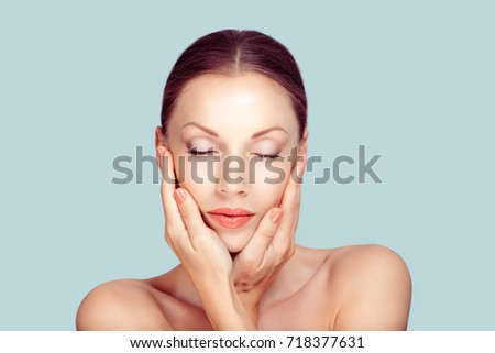 Beauty face of the young beautiful woman eyes closed - isolated on light blue #718377631