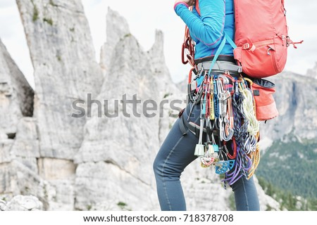 Close-up of mountaineer with trad climbing rack including backpack, chalk bag, harness with spring-loaded cams, nuts, quickdraws, slings and carabiners preparing for ascent in summer mountains #718378708