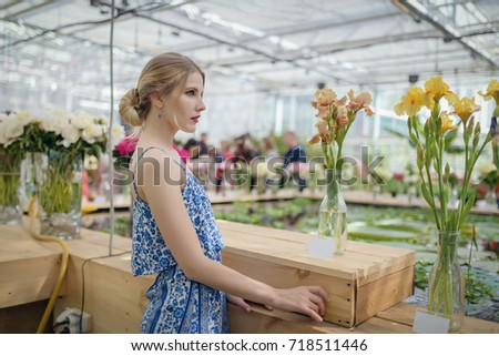 Portrait of beautiful young woman among the flowers. #718511446