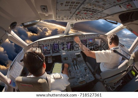Cockpit of a modern passenger aircraft. The pilots at work. Royalty-Free Stock Photo #718527361