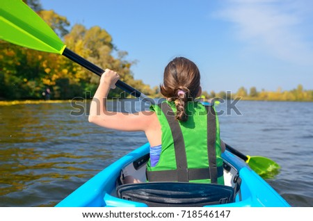 Family kayaking, child paddling in kayak on river canoe tour, kid on active summer weekend and vacation, sport and fitness concept  #718546147
