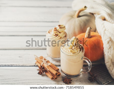 Pumpkins spice latte with pumpkins and withe cozy sweater over white wood texture. Copy space.  Royalty-Free Stock Photo #718549855