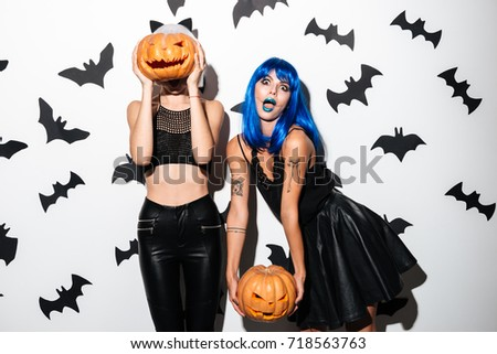 Picture of two emotional young women in halloween costumes on party over white background with pumpkin.