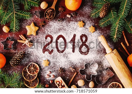 Happy New Year 2018 written on flour and Christmas Decorations Gingerbread cookies, cinnamon, oranges, spices, nuts and cookie cutters on wooden background. Christmas card, New Year greeting card #718571059