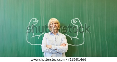 Strong senior teacher with chalk muscles in front of chalkboard #718581466