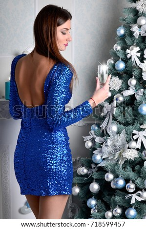 Young beautiful girl in an elegant blue dress around a Christmas tree raises a glass of champagne during the New Year celebration. European Christmas traditions #718599457