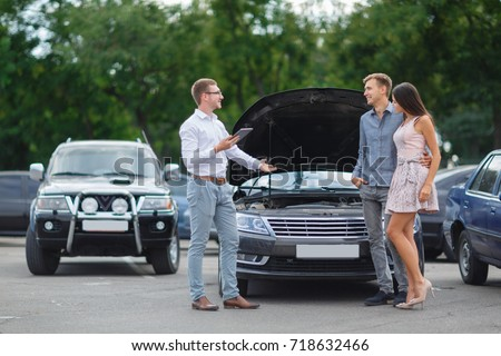 Buying used car. Car Dealer Inventory. Used cars store. Male wants to buy the car. Happy life. Summer time. Young family. Communication with the seller from auto for sale. Royalty-Free Stock Photo #718632466