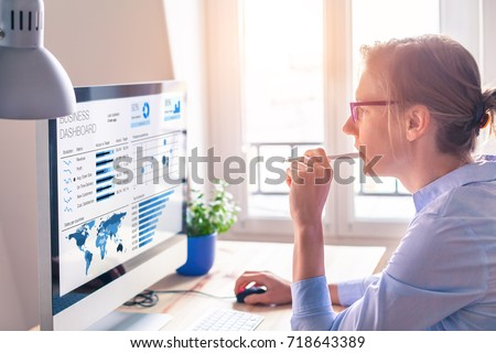Businesswoman looking at business analytics (BA) or intelligence (BI) dashboard on the computer screen with sales data statistical report and key performance indicators (KPI) Royalty-Free Stock Photo #718643389