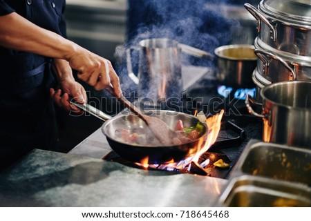 Chef stirring vegetables in frying pan #718645468