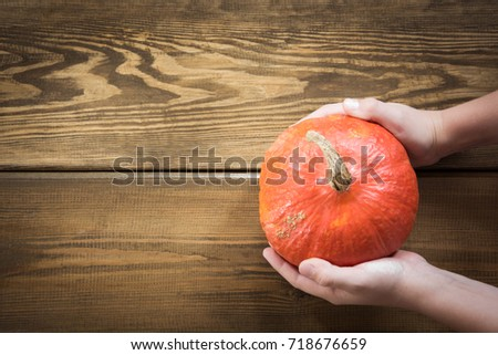 Pumpkin in child's hands on wooden board. Top view and copy space. Harvest. #718676659