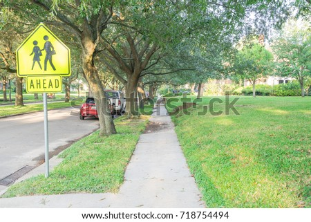 Side view of residential street covered by live oak arched tree branches at upscale neighborhood in Houston, Texas. Car parked on street, school zone sign. America is excellent green, clean country