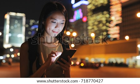 Asian Woman working on mobile phone in city at night #718770427