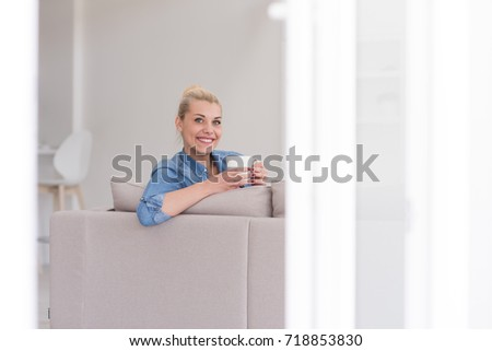 beautiful blonde woman enjoying a cup of coffee while sitting on a sofa in her apartment #718853830