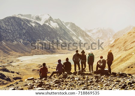 Group of friends or tourists stands at mountains viewpoint. Travel or tourism concept #718869535