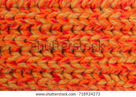 Winter orange knitted scarf close-up. #718924273