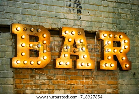 Bar signboard. Inscription from large metal letters decorated with glowing light bulbs on the brick wall