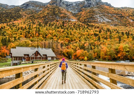 Autumn nature hiker girl walking in national park in Quebec with backpack. Woman tourist going camping in forest. Canada travel hiking tourism at Hautes-Gorges-de-la-Riviere-Malbaie National Park. #718962793