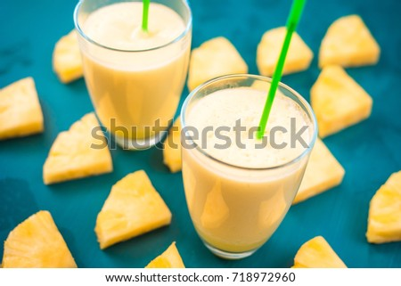 Pineapple smoothie with fresh pineapple on wooden blue table. #718972960