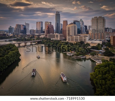 Over Lady Bird Lake in Austin, Texas featuring riverboats and the downtown skyline during sunset #718991530