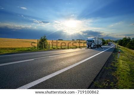 Trucks on the asphalt road along a field with golden grain in rural landscape at sunset #719100862
