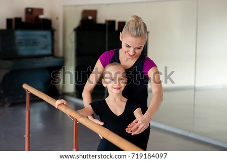 The choreographer teaches the child the ballet positions #719184097